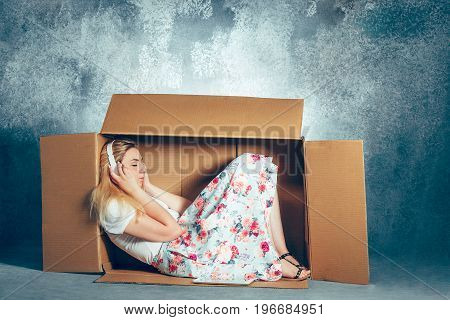 Introvert concept. woman sitting inside box and working with laptop and headphones