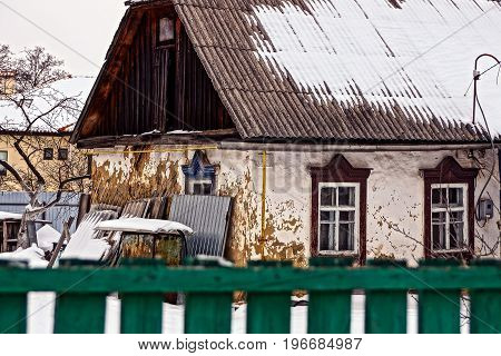 An ancient cottage behind a fence in a winter yard
