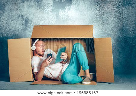 Introvert concept. Man sitting inside box and working with phone and laptop