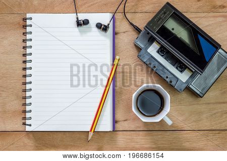 Bank notebook with pencil laying on the brown table. Vintage old tape player with earphones and black coffee put on the table as well.