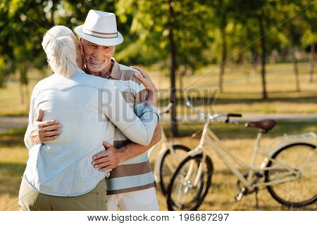 See you later. Positive delighted male person embracing his woman, keeping smile on face while looking downwards