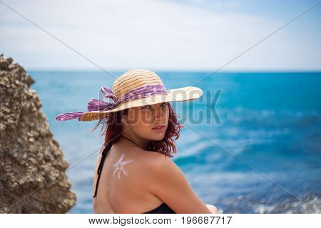 A Young Girl On A Beach With A Hat, Sun And Enjoys The Sun, On The Shoulder Drawn Sun From Sun Cream