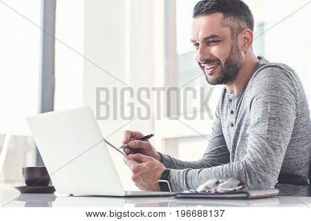 Laboring with pleasure. Joyful trendy employee is sitting with notepad and pen while looking at screen of laptop with smile. Copy space in the left side