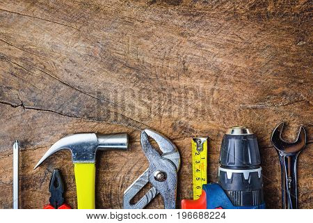Top view of Working toolswrenchhammerscrewdriverplierelectric drilltape measuremachinist square on wooden rustic background. flat lay.