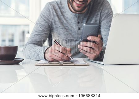 Doing work properly. Cheerful manager wearing casual clothes is making some notes while holding his smartphone. He is sitting at desk with laptop and cup of coffee against window