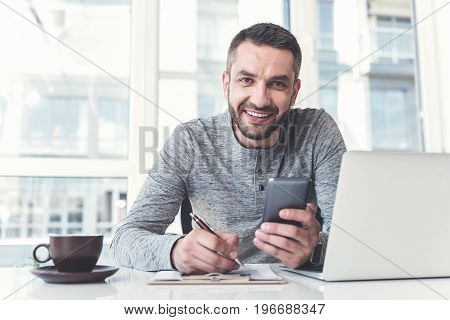 Confident expert. Portrait of positive attractive manager is making some notes and holding his mobile phone while sitting at table with laptop. He is looking at camera with joy