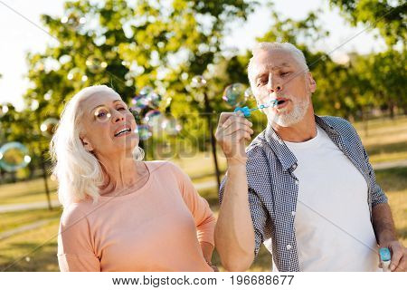 Enjoying walk. Enigmatical female person standing near her husband and keeping smile on face while looking upwards