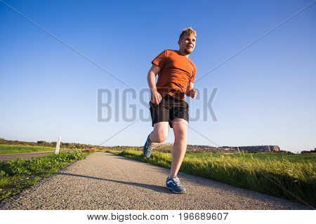 Man running outdoor sprinting for success. Male fitness runner sport athlete in sprint at great speed in beautiful landscape.