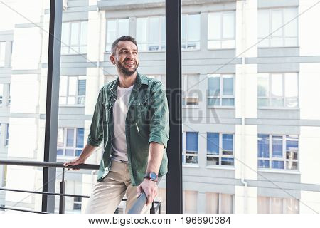 Feeling happy. Positive attractive adult guy wearing casual clothes is leaning on railing and looking aside with smile. Copy space in the right side