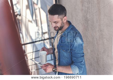 Great news. Top view of pleasant positive bearded guy is drinking espresso while reading message on tablet with smile