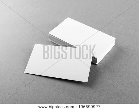Photo of blank business cards on gray paper background. Template for branding identity. Mockup for ID. Studio shot.