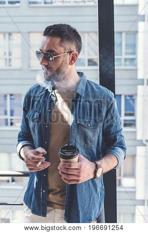 Enjoying bad habits. Confident serious man with stubble is exhaling smoke while standing with coffee and cigarette. He is looking aside thoughtfully