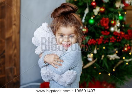 A little baby hugs a beaded toy. The concept of Christmas and New Year.