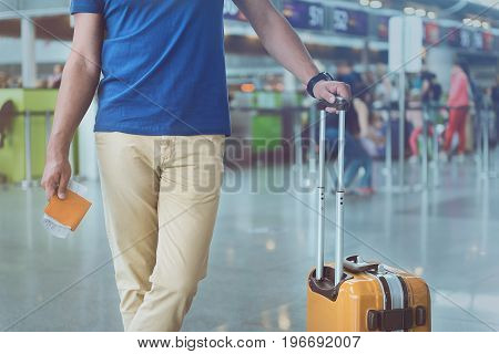 He is ready for trip by plane. Male passenger putting hand on baggage handle and holding tickets. Close up