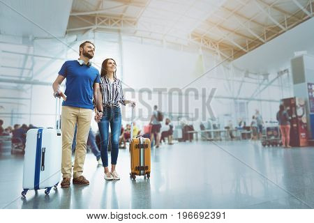 Hilarious passengers are standing in hall of airport and looking ahead with bright smile. They have own luggage. Low angle. Copy space on right side