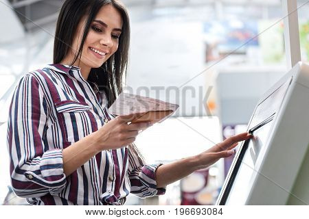 Joyous woman is using device for self check-in in airport. She typing on screen and looking at ticket. Portrait. Low angle