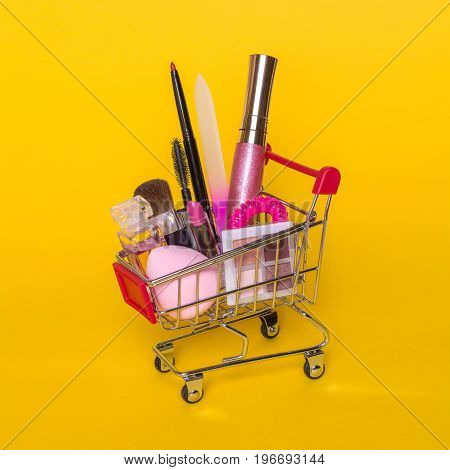 Creative concept with shopping trolley with makeup on a yellow background. Perfume, sponge, brush, mascara, pencil, nail file, eye shadow, lip gloss in the basket