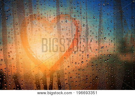 Heart shape on glass with water drops background.