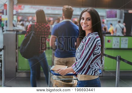 Hilarious woman is carrying her luggage and looking at camera with smile. She standing in line for registration. Portrait
