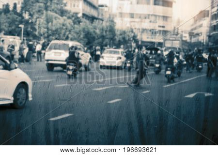 People in the city on a rainy day with blurred images.