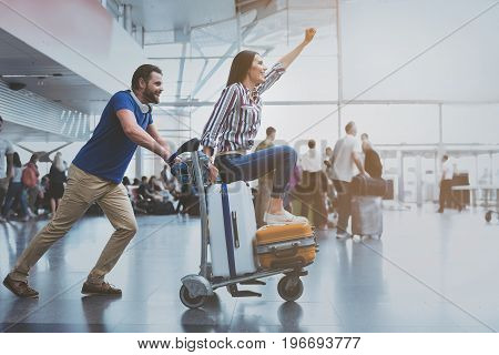 Cheerful lady is sitting on luggage and man pulling small cart. They are having fun