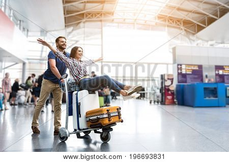 I believe I can fly. Cheerful woman is sitting on baggage and man pulling cart forward. They looking ahead with joyous smile. Copy space on right side