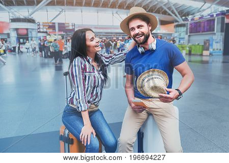 Happy woman is putting hat on her boyfriend head. They are glancing at each other with smile. Portrait