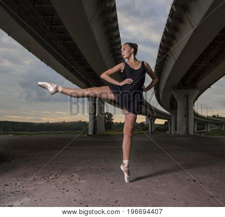 Gracefull ballerina on the streets. Ballerina out of doors, young modern ballet dancer posing on the background of the bridge