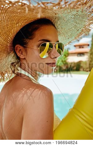 Girl in a sun hat next  the pool