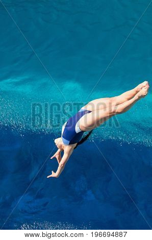 Young Woman Diving In To The Swimming Pool, High Angle View