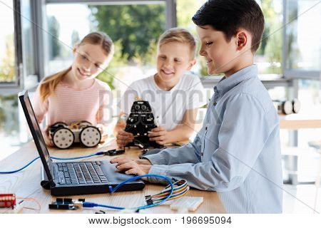 Interesting task. Joyful little boy using the laptop and changing settings of his own robot while his friends observing the process with curiosity