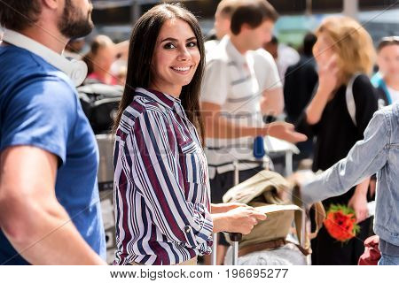 Happy woman is standing among crowd at airport-foyer and looking at camera with bright smile. Portrait