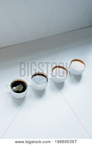 Different Kinds Of Coffee In Row On White Table, Close-up View