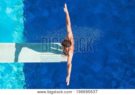 Young Man Diving In To The Swimming Pool, High Angle View