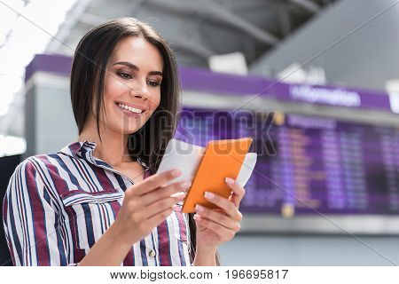 Ready for trip. Joyful young woman is standing at airport while looking at her ticket and passport with smile. She is standing against timetable board. Copy space in the right side