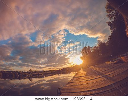 Landscape water river lake mooring surface reflecting mirror sky at sunset dawn. Wide angle action camera go pro.