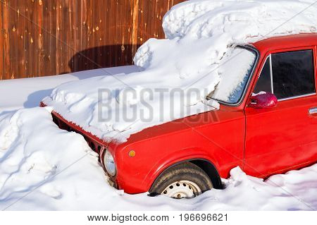 Old red car in the snowdrift near the fence