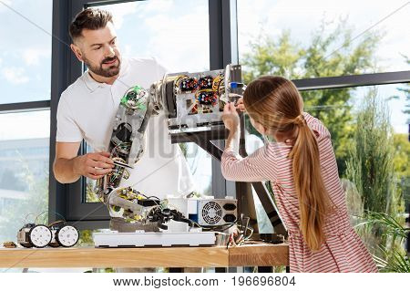 Helpful kid. Fair-haired teenage girl plugging some wires into the arm part of a human robot thus helping her teacher