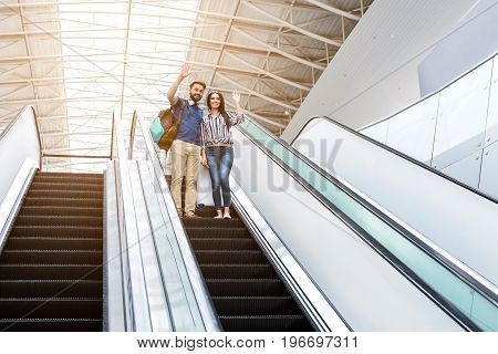 Unbelievable trip. Low angle of joyful happy couple is waving from escalator at airport while getting down with baggage and looking aside with smile. Copy space in the right side