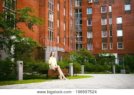 Portrait Of A Young Pretty Woman In Blue Denim  Jeans Shorts Sitting On A Bench In Courtyard Of A Re
