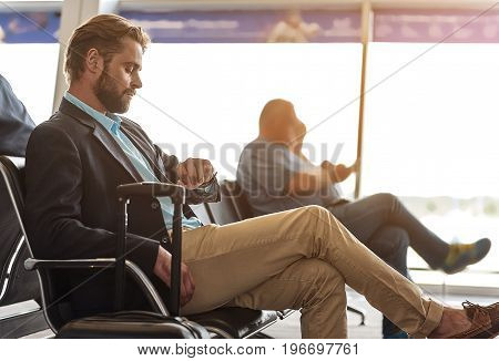 Waiting for plane. Profile of adult serious businessman wearing casual style clothes is sitting on bench in international airport and looking at his watch to checking time. Copy space in right side