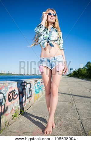 Slim young blond woman in jeans shorts posing outdoors