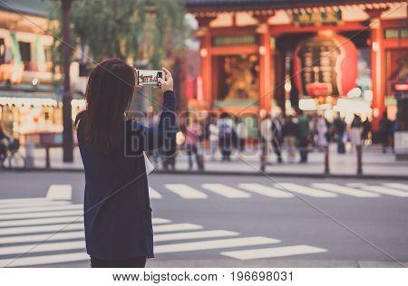 Female asian tourist using smartphone for taking photo of giant lantern at Sensoji Shrine (temple) Asakusa Tokyo Japan.