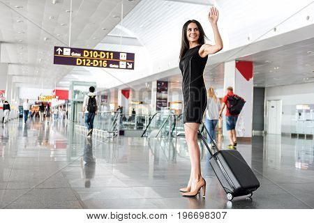 See you soon. Cheerful elegant business woman with suitcase is waving goodbye while going to boarding gate at international airport. Copy space in left side