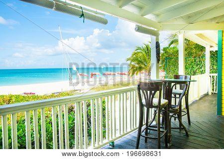 Turks and Caicos Island, July 10, 2012; Shady tropical veranda seats overlooking sun umbrellas on Caribbean beach and ocean blue sky and horizon.