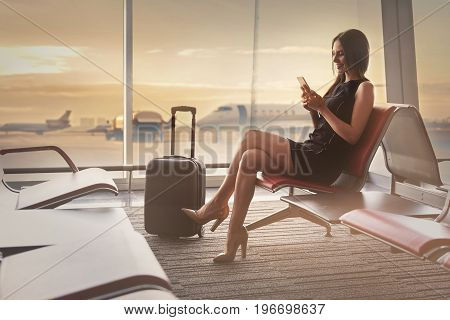 Always in touch. Young elegant business woman is sitting with smile while using mobile phone at waiting hall against big window. Copy space in left side