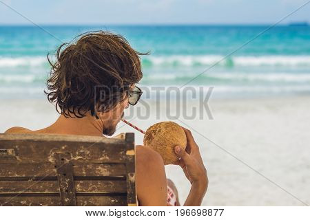 Young Man Drinking Coconut Milk On Chaise-longue On Beach.