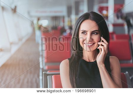 Pleasant call. Portrait of happy business lady is waiting at modern airport for departure while having communication on smartphone. Copy space in left side