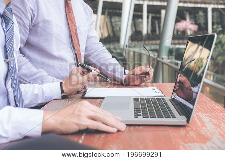 Co working conference Business team meeting present investor executive colleagues discussing new plan financial graph data on outdoors office table with laptop and tablet Finance accounting investment.