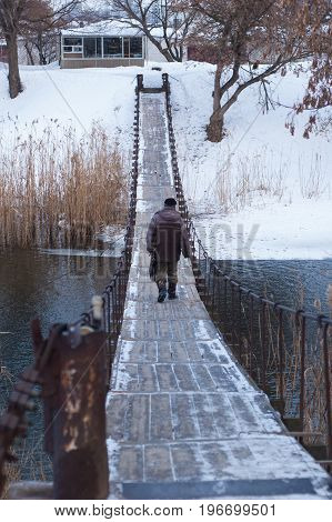 A man walks the pontoon bridge across the river in winter.